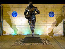 Statue of Dean in football kit with ball