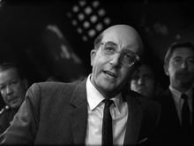 Sellers with bald head and thin-rimmed glasses looking at the camera with head slightly tilted
