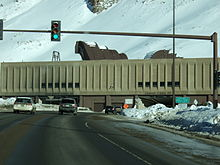 partial view of a traffic signal leading to a hole in a snow covered building.