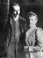 Nineteenth century photograph of a man in his 30s and a middle-aged woman standing side by side. He has a large moustache, and is looking at the woman; she is looking straight at the camera.
