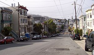 Eureka Valley, looking north on Castro Street from 20th. The giant rainbow flag at Castro and Market is just visible. In the summer months, fog tends to roll in over Twin Peaks and other hills to the west in the evenings and retreat again the next morning.