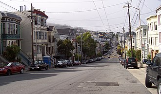Eureka Valley, San Francisco - Eureka Valley, looking north on Castro Street from 20th. The giant rainbow flag at Castro and Market is just visible. In the summer months, fog tends to roll in over Twin Peaks and other hills to the west in the evenings and retreat again the next morning.