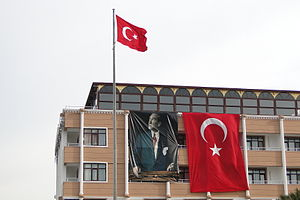 Atatürk's cult of personality - A building facade with Turkish flags and a banner of Atatürk.