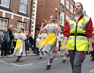 First aid - First aider of the British Red Cross accompanies parade of morris dancers at the Knutsford Royal May Day 2012