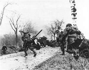 Battle of the Bulge - German troops advancing past abandoned American equipment