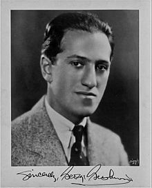 Head and shoulders picture of a young man with slicked back dark hair and a signature on the bottom
