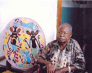 """George Lilanga - George Lilanga with a modern masonite painting by the title: we banana anangalia ulimi kiangu unawasha (""""Banana look to me, I have the mouth-watering"""")"""