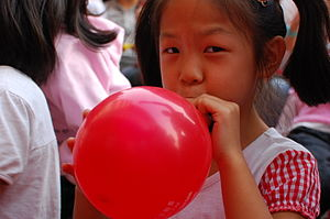 Girl inflating a red balloon by blowing into it.