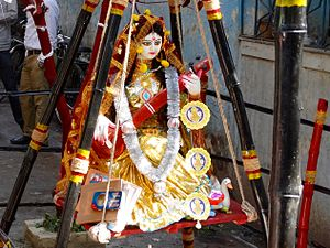 Vasant Panchami - Goddess Saraswati dressed in yellow sari on Vasant Panchami, Kolkata. She sits in a swing, holding a veena, with books in one corner.