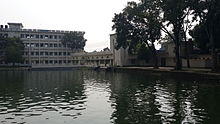 Large pond and college buildings