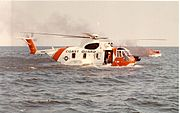 HH-3F Pelican on the water with a burning boat