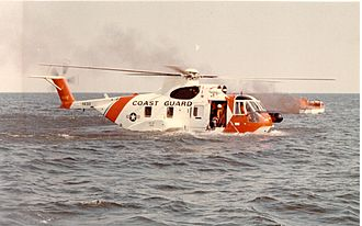 Amphibious helicopter - An HH-3F Pelican helicopter of the United States Coast Guard lands on the water near a burning boat.