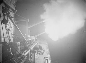 HMS Orion (85) - Flashes from the 6-inch guns of Orion can be seen against the darkness during a nighttime bombardment of enemy positions on the Garigliano River