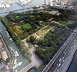Bird eye view of a park with grassland, trees and ponds surrounded by tall buildings and a big street.