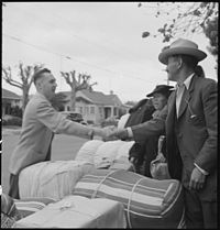 Hayward, California. Friends say good-bye as family of Japanese ancestry await evacuation bus. Bag . . . - NARA - 537514