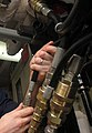 Hoses and fittings from US Navy 081105-N-2456S-004 Aviation Structural Mechanic Airman Marty Baum connects hydraulic lines to the hydraulic drive unit (cropped).jpg