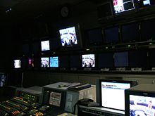 TV director's console, with many monitors on wall