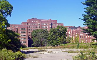Hudson River State Hospital - The Cheney Building as visible from a nearby strip mall, with Ryon Hall to the right.