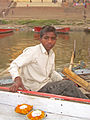 India - Varanasi - 012 - kids row by selling puja flower candle boats (2147059656).jpg