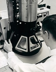 A black-and-white photograph of a young man examining a large microscope. The man has short, dark hair, is wearing a white shirt and a white lab coat and is holding a smoking pipe in his mouth. The microscope has a black conical base with three trapezoidal windows and a silver cylindrical body.