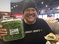 Jimmy John's Owner Proudly Holds A Jimmy John's Sandwich and Fresh Greenery.jpg