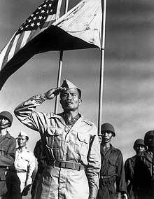 Filipino male in World War II Army Khaki uniform saluting in the foreground. A color guard in the background; the 48-star United States flag on the viewers left, a reversed/war Philippine Commonwealth flag on the viewers right.