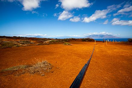 Irrigation tubing running atop the red soil of Kaho`olawe as a crew works to plant new life in the hard-packed ground. Kahoolawe restoration work.jpg