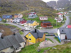 Centre of village, taken from near the Kamøyfjord light. On the right, the Fv172 road comes from the south and proceeds through the centre before heading south again on the left of the picture. The two blue-painted houses on the left hand side of the picture are part of the group of houses which make up the Arran guesthouse. The top floor of the yellow house in the bottom centre of the picture contains the Gallery East of the Sun.