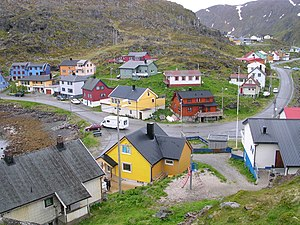 Kamøyvær - Centre of village, taken from near the Kamøyfjord light. On the right, the Fv172 road comes from the south and proceeds through the centre before heading south again on the left of the picture. The two blue-painted houses on the left hand side of the picture are part of the group of houses which make up the Arran guesthouse. The top floor of the yellow house in the bottom centre of the picture contains the Gallery East of the Sun.
