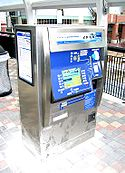 A silver and blue ticket vending machine on a station platform with payment options and digital screen visible.