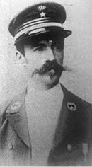 Portrait photograph of a young man wearing a military uniform with a prominent moustache