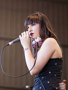 A 19-year-old woman is shown in upper body, left profile. She holds a microphone close to her lips using her left hand, the cord is looped back to her hand. Her right arm is clenched behind her back. She wears dark brown hair, her dark blue dress has a pattern of small yellow-white logos, and a large flower is near her shoulder. Her left wrist has a bracelet and her eyes are directed to her left. Beyond her the wall of the venue is blurred.