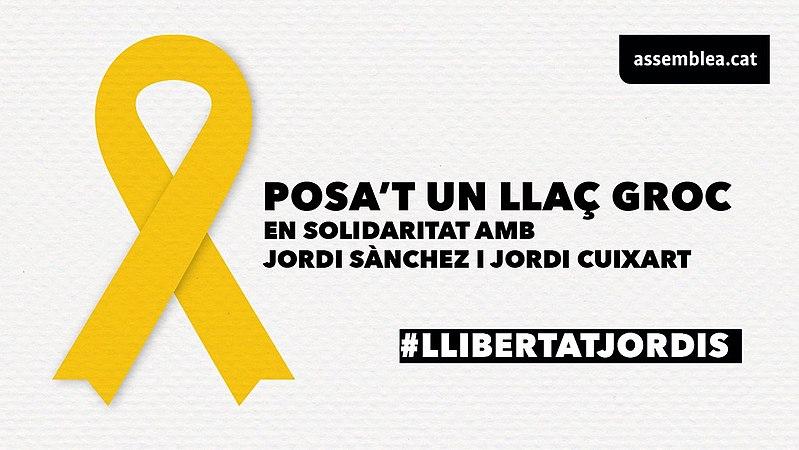 Cartel de la Asamblea Nacional Catalana, pidiendo ponerse un lazo amarillo en solidaridad con Jordi Sànchez y Jordi Cuixart.
