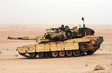 color photo of an Abrams tank sitting in an open sandy field