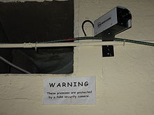 "Camera on a concrete block wall, over a sign reading ""WARNING: These premises are protected by a fake security camera"""