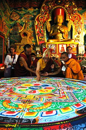 Sakya Pandita - Dagchen Rinpoche closes the Hevajra Mandala of colored sand using a gold dorje below statue of Sakya Pandita