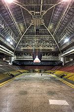 Интерьер арены.  Сиденья разного цвета, высокий сводчатый потолок.