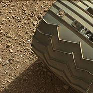 Martian gravel beneath one of the wheels of the Curiosity rover