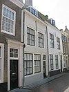 foto van Huis met geverfde rechte gevel, de gootlijst op klossen