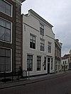 foto van Huis met geverfde, aan de hoeken ingezwenkte lijstgevel met hardstenen band aan de voet