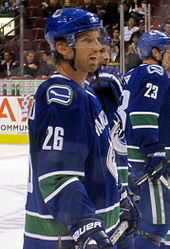 A Caucasian ice hockey player in his mid-thirties. He wears a blue jersey with white and green trim and a blue, visored helmet. He looks forward with his mouth slightly parted in a relaxed stance.