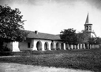 Mission San Juan Bautista - A photograph of Mission San Juan Bautista taken between 1880 and 1910. The steeple (far right), constructed after the mission was secularized, was subsequently destroyed in a fire.