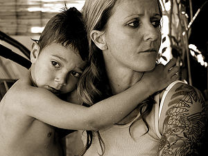 English: Mother with tatooed arm and wet child.
