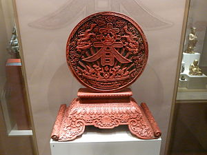 Museum of Asian Art of Corfu - Ritual disc on a base, Beijing-red lacquer. Relief décor and the ideogram of spring on a green background, 17th-19th century.