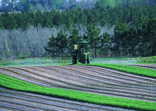 Farmer spraying pesticides, Georgia, USA