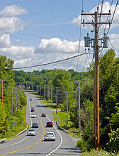 A road, with wooden telephone poles and lines on either side, descending from the camera into a wooded area and then ascending in the background. Cars are traveling it in both directions.