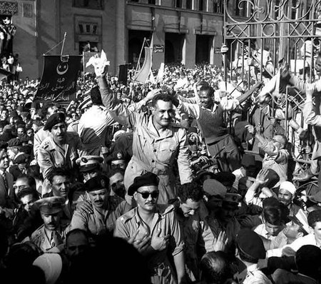 A man standing in an open-top vehicle and waving to a crowd of people surrounding the vehicle. There are several men seated in the vehicle and in another trailing vehicle, all dressed in military uniform