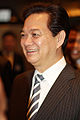 a smiling man with black hair, dressed in a suit and a black-white tie