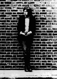 A black-and-white photograph of a man leaning against a brick wall, with his hands resting on his waist.
