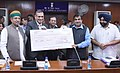 Nitin Gadkari being received a dividend cheque by the CMD, National Projects Construction Corporation Ltd., Shri Sanjay Kundu, in New Delhi.jpg